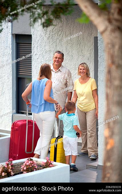 Young mother and little son coming to visit grandparents. Happy man and woman meeting daughter and grandson by the house