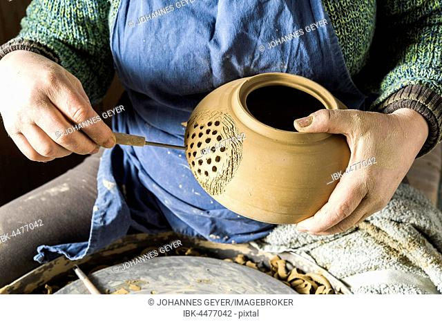 Ceramics workshop, hand drilling holes into pot with hole cutter for tea strainer, Pittenhart, Upper Bavaria, Germany