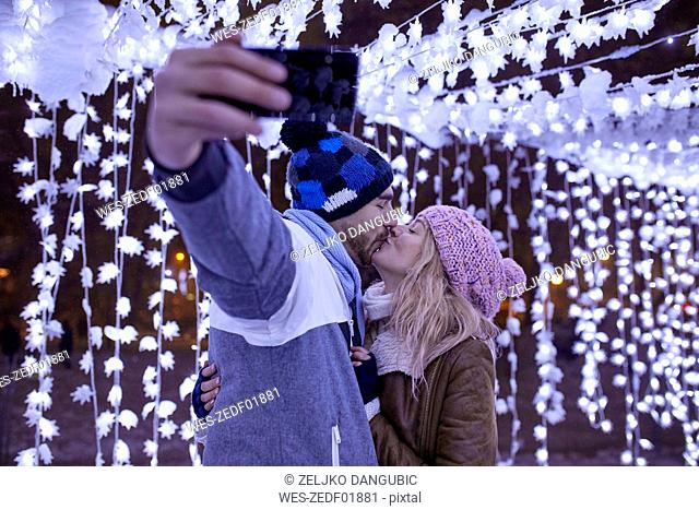 Young couple in winter decoration kissing and taking a selfie