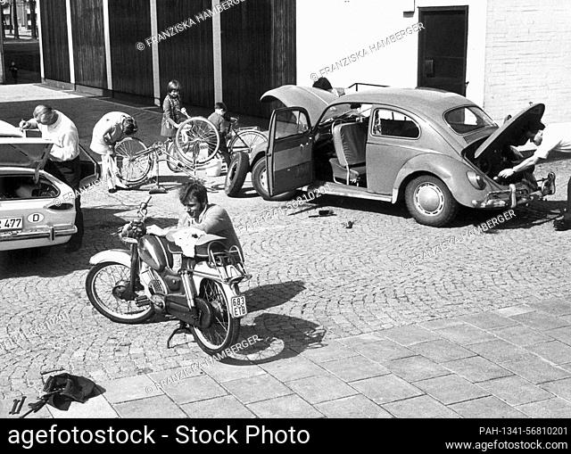 Children and adults clean their bikes, cars and mopeds on a farm in Munich. Photo taken in March 1970. The mild and early spring weather before the Easter...