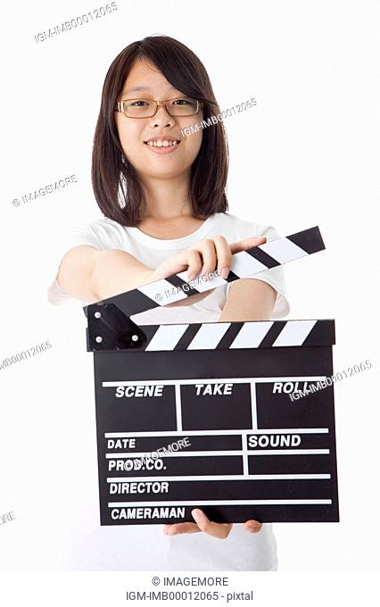 Teenage girl holding film slate and smiling at the camera