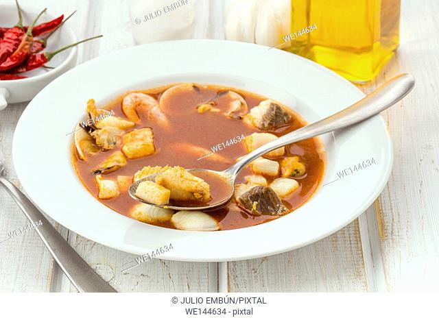delicious plate of seafood soup with spoon in modern wooden table