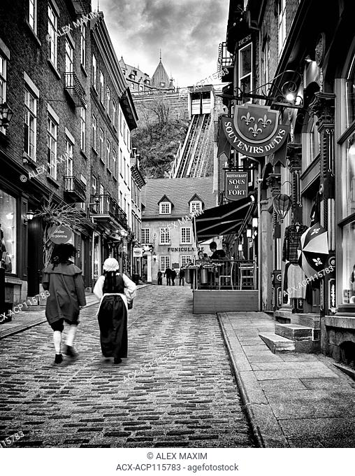 Two people in medieval costumes walking up the Rue Sous Le Fort street in old Quebec City with funicular in the background. Black and white photo