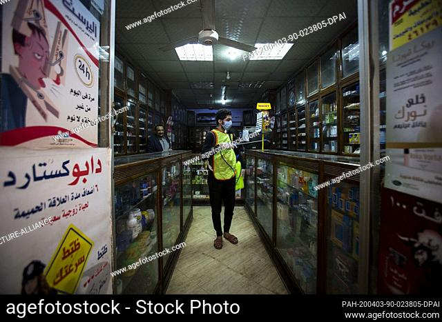 03 April 2020, Egypt, Shubra Al Khaymah: A volunteer wearing a face mask sprays disinfectant at a paharmacy to help to help curb the spread of the Coronavirus...