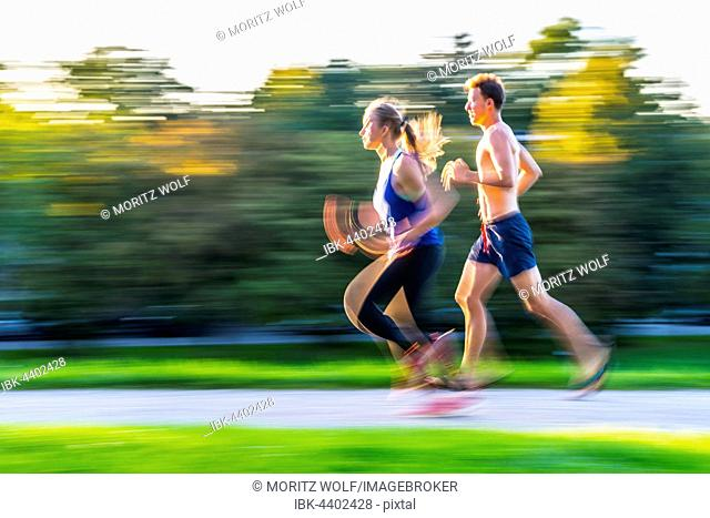 Panning shot, young woman and young man in sportswear jogging through park, Munich, Upper Bavaria, Bavaria, Germany