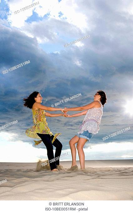 Girlfriends twirl in sand