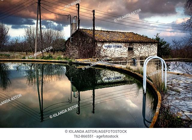 Abandoned house reflected in the water of a reservoir  Tarragona, Spain