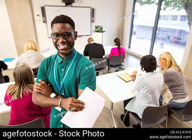 Portrait confident male community college instructor in classroom