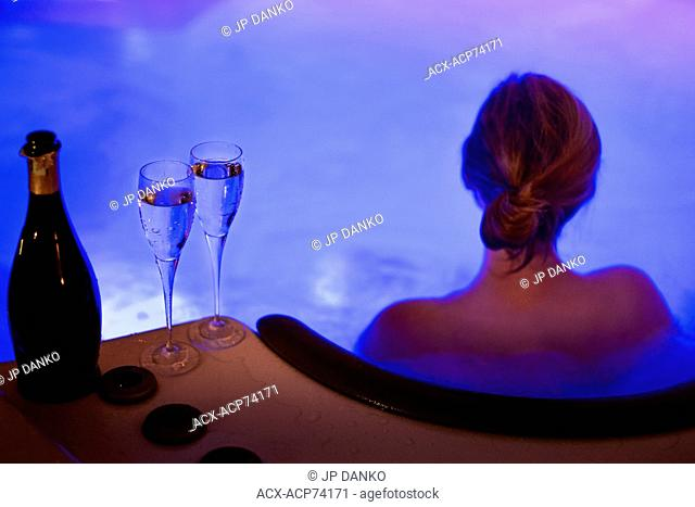 Attractive women relaxing in hot tube and drinking champagne on New Years Eve