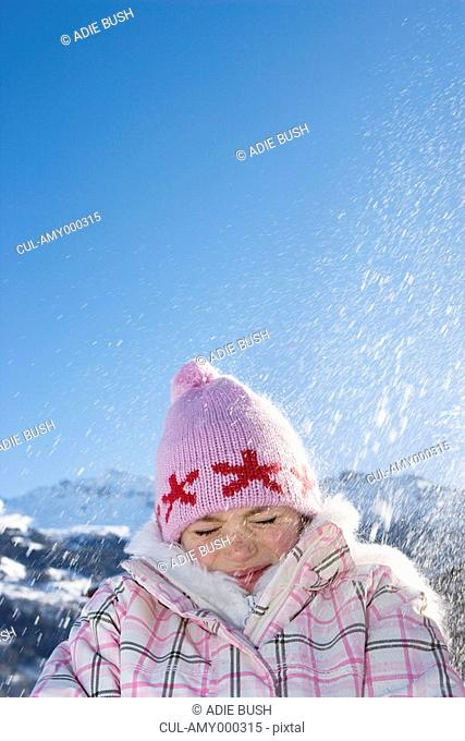 Young girl with snow falling on her