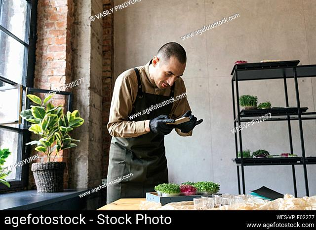 Man taking smartphone picture of microgreens on table