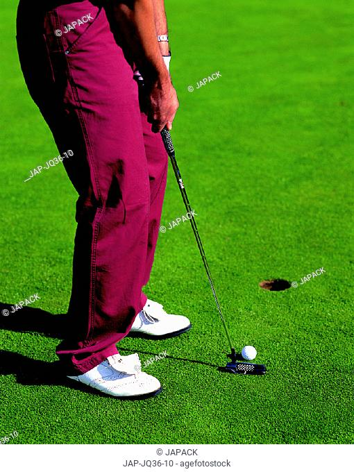 Golfer taking putt on green
