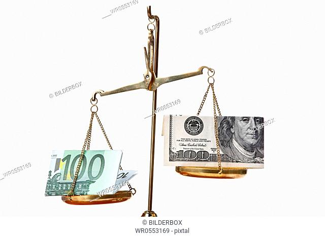 Euro notes and dollar on scales.Isolated against a white background
