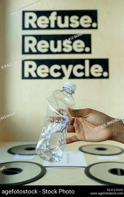 Hand recycling plastic bottle in bin below recycling sign
