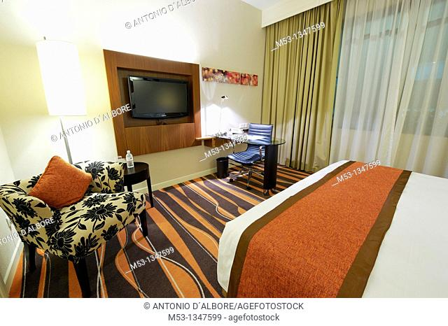 A room of a five star luxury hotel featuring a flat screen television set, a working desk a cozy sofa and few trendy lamps