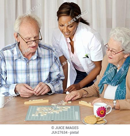 A senior couple and care assistant playing a board game together