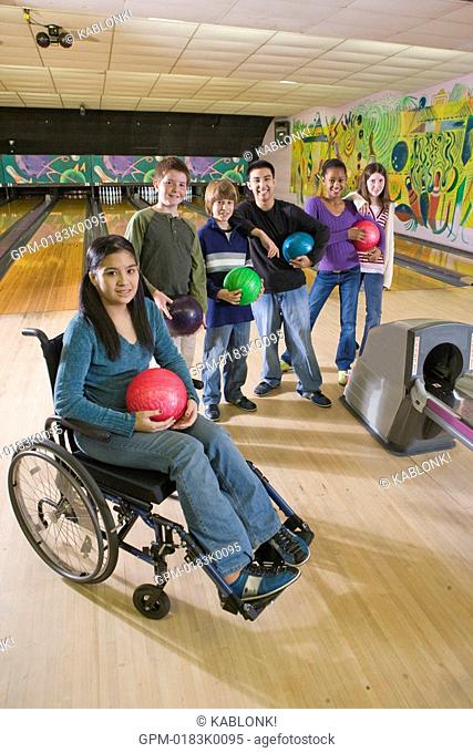Portrait of multi-ethnic teenagers holding bowling balls and girl in wheelchair at bowling alley
