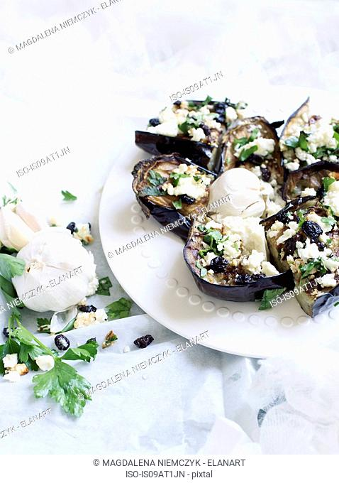 Still life plate of stuffed aubergines with ricotta and herbs