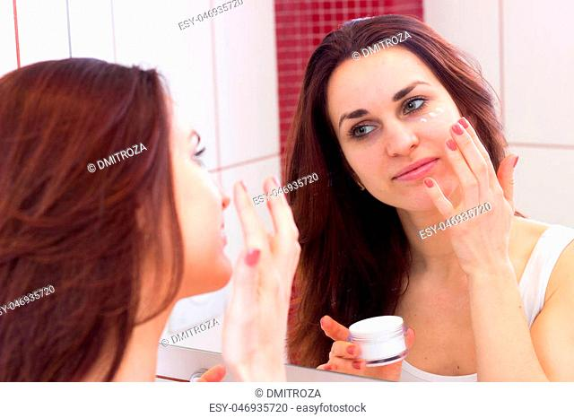 Beautiful young woman with dark long hair in white shirt using face cream in front of the mirror in her bathroom