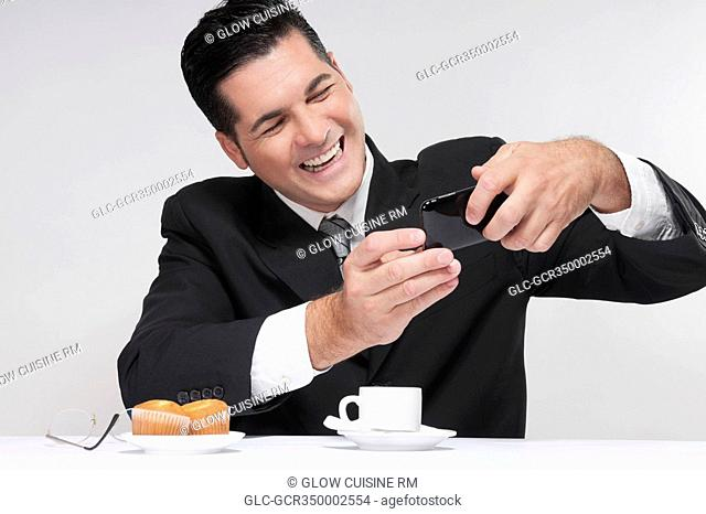 Businessman using a mobile phone over a cup of coffee