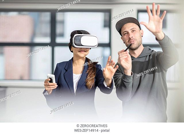 Man instructiong businesswoman wearing VR glasses in office