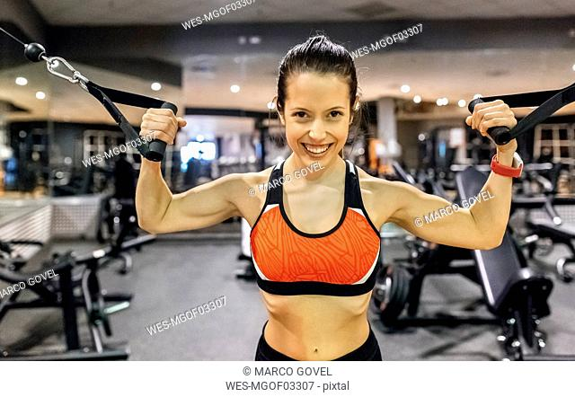 Portrait of a happy young woman working out in gym