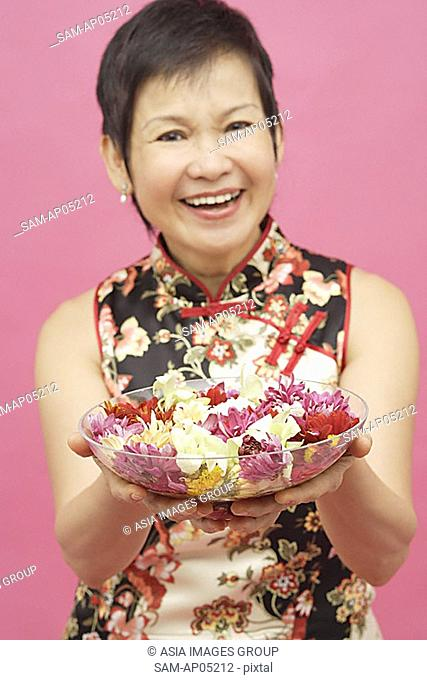 Mature woman holding bowl of flowers