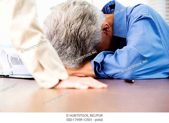 View of a tired business man resting his head on a table