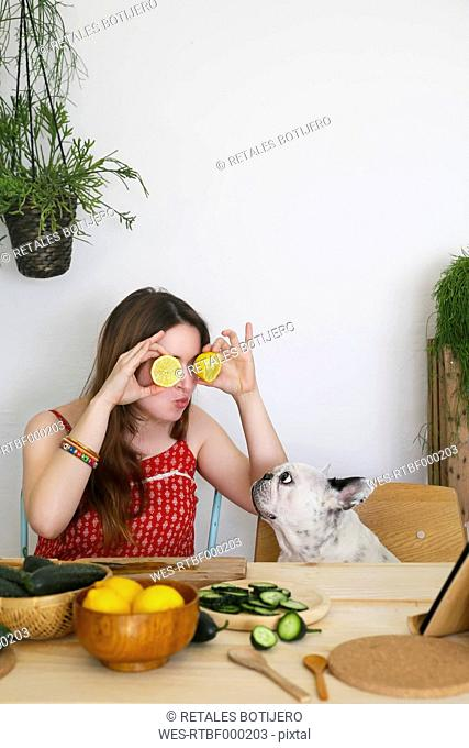 French bulldog watching woman covering her eyes with lemon halves