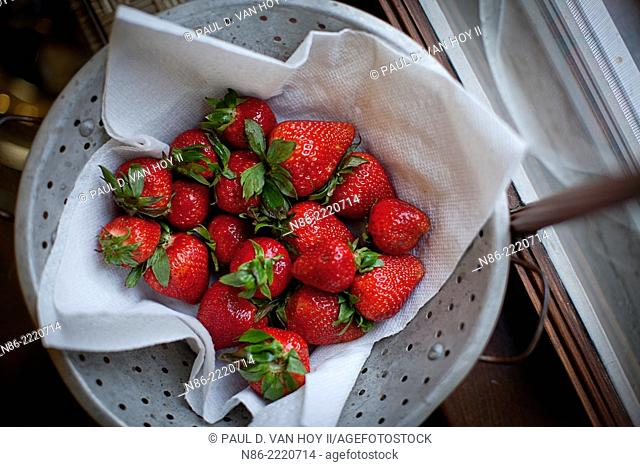 fresh whole strawberries in colander