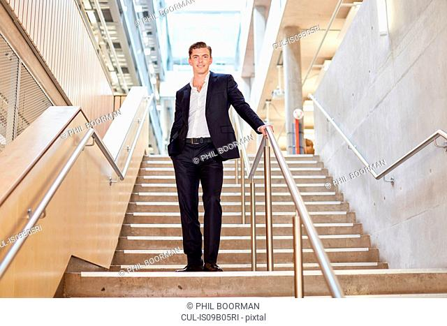 Portrait of young businessman standing on office stairway