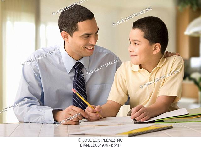 Hispanic father helping son do homework