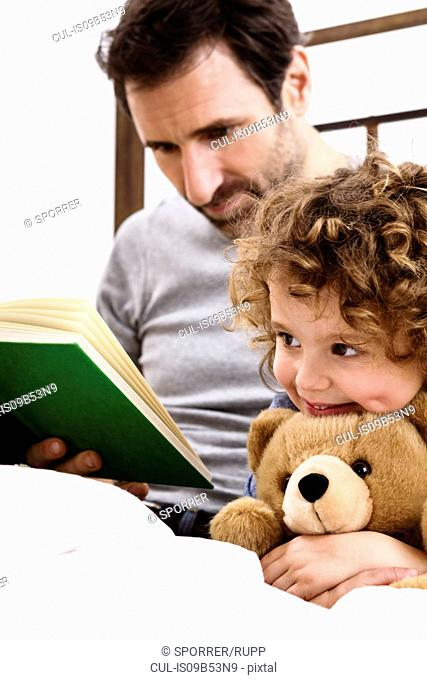 Girl hugging teddy bear while father reads storybook in bed