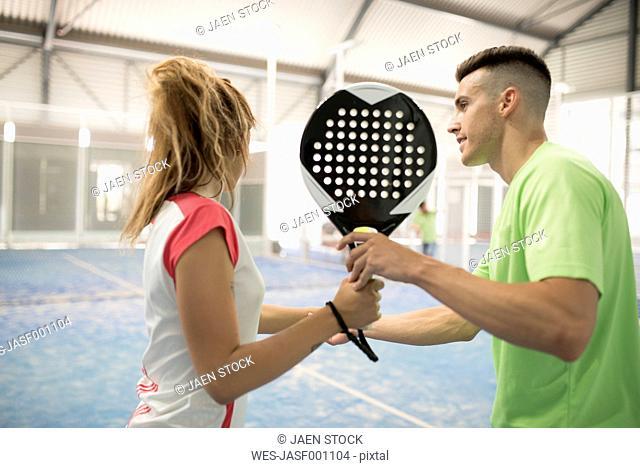Man teaching woman in paddle tennis