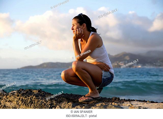 Mid adult woman crouching and gazing at caribbean sea from pier, Spice Island beach resort, Grenada