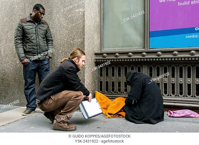 New York, USA, Male social workers with Goddard Riverside, reaching out to a homeless person, living in the streets of Manhattan
