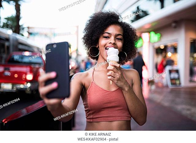 USA, Nevada, Las Vegas, happy young woman eating ice cream in the city taking a selfie