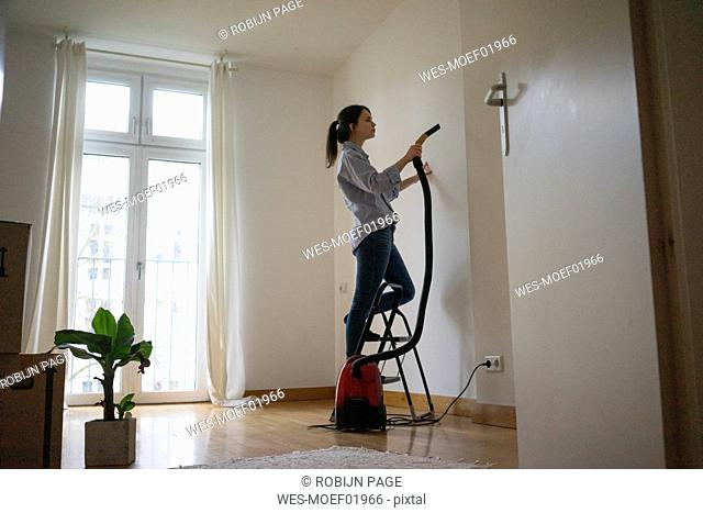 Young woman standing on step ladder, hoovering her new home