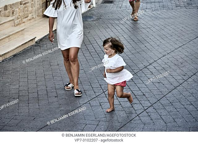 daughter running on street next to mother