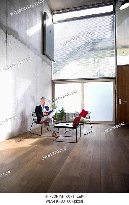 Businessman sitting in a loft at concrete wall reading book