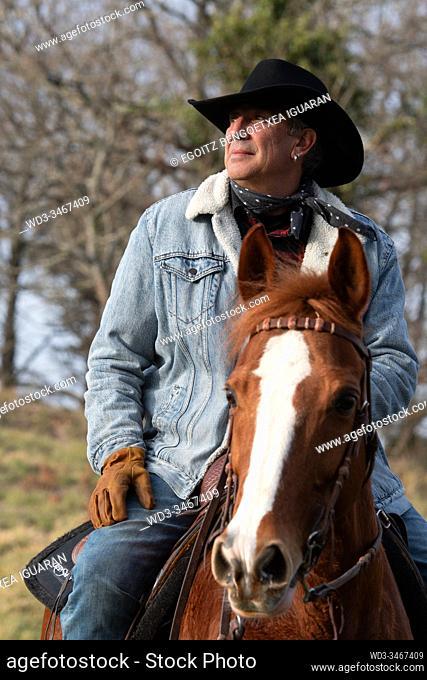 Close-up frame of a veteran cowboy man riding his arabian horse