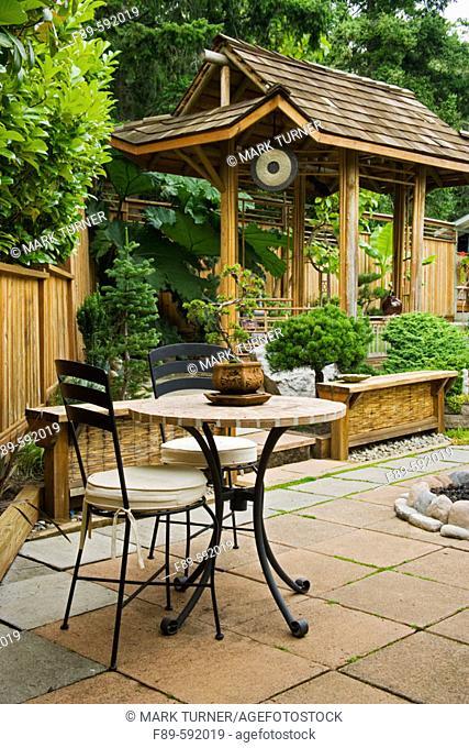 Bonsai on patio table in front of Japanese-style teahouse. Lehmann, Bellingham. Washington. USA