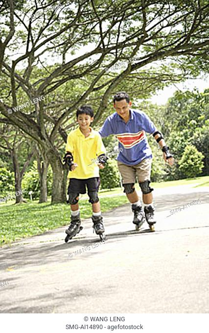 Father and son roller blading in park
