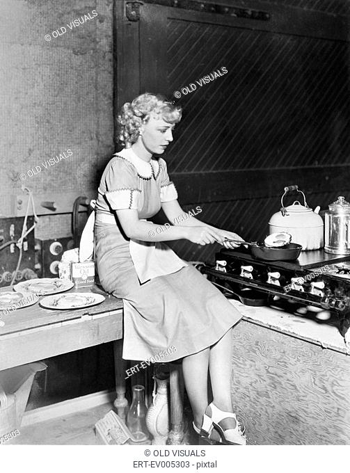 Young woman sitting on the counter and cooking food in the kitchen All persons depicted are not longer living and no estate exists Supplier warranties that...