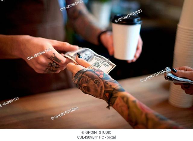 Customer paying for her coffee with cash