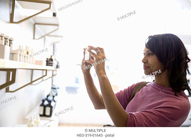 Woman with camera phone photographing merchandise on shelves in home fragrances shop