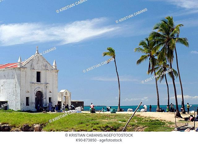 The white washed Church of Santo Antonio with palm trees, people and blue sky in Stone Town on the Ilha de Mocambique (Island of Mozambique)