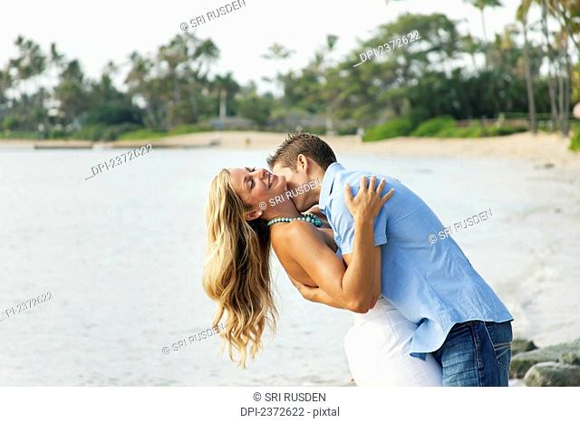 Portrait of a couple kissing on a beach at the water's edge; Honolulu, Hawaii, United States of America