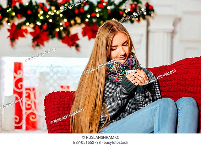 Beautiful girl is warming near fireplace while holding a cup of coffee in her hands