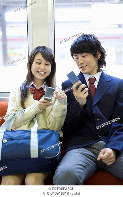 Girl and boy on the train, holding mobile phones on the seat, smiling